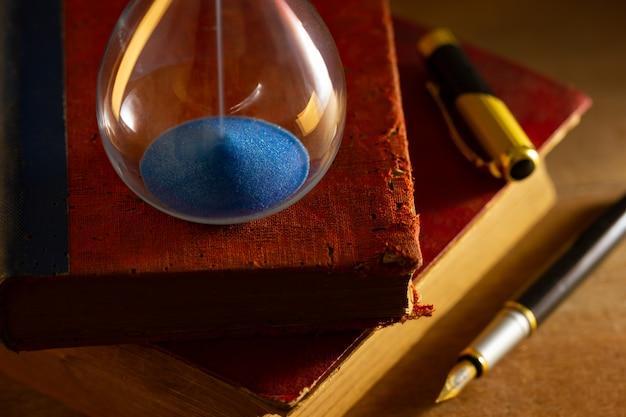 Ampulheta no livro velho na luz da manhã. hora de ler um livro.