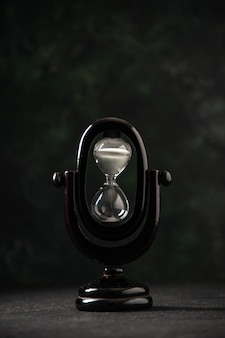 Ampulheta projetada de frente na cor preta em superfície escura