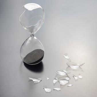 Ampulheta quebrada. perda de tempo. fim da oportunidade.