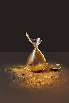 Ampulheta quebrada vintage antiquada verticalmente em pé com pedaços de vidro e areia dourada em uma parede escura duotônica, copie o espaço.