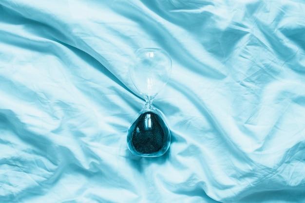 Ampulheta transparente na cama azul com copyspace