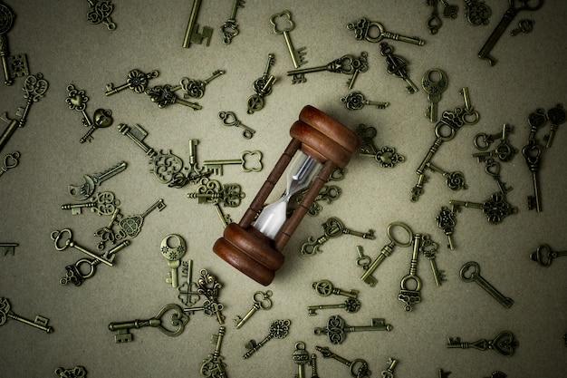 Ampulheta velha e chaves clássicas no fundo de papel marrom