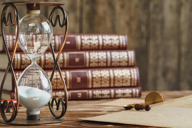 Ampulheta vintage contra uma pilha de livros antigos