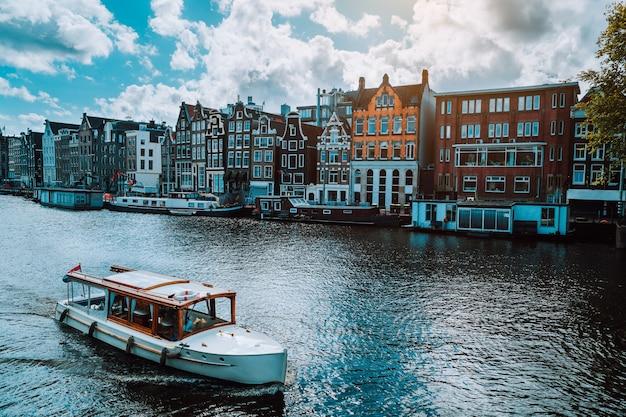 Amsterdam holanda dançando casas ao longo do rio amstel, marco na paisagem da velha cidade europeia. nuvens pitorescas em um dia ensolarado de outono.