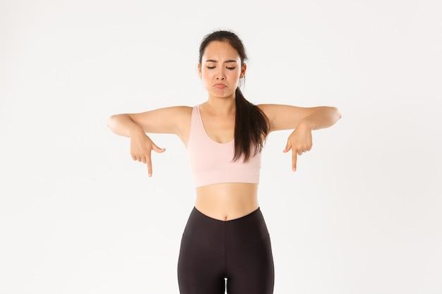Amuada e decepcionada garota asiática treino, atleta feminina em activewear franzindo a testa chateada, apontando e olhando para a coisa ruim, fundo branco.