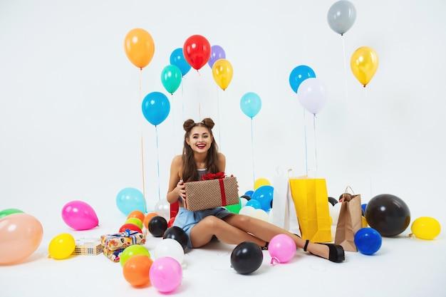 Amuzed menina adolescente depois da festa de aniversário. segurando uma enorme caixa de presente