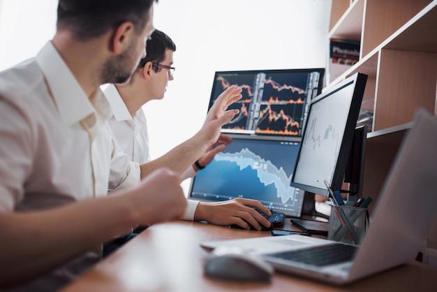 Analisando dados. close-up da equipe de jovens negócios trabalhando juntos em um escritório criativo enquanto jovem mulher apontando para os dados apresentados no gráfico com uma caneta.