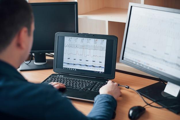 Analisando informações. o examinador de polígrafo trabalha no escritório com seu equipamento detector de mentiras