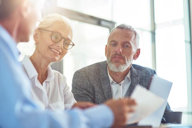 Analisando o relatório de executivos bem-sucedidos trabalhando juntos, sentados à mesa em um escritório moderno