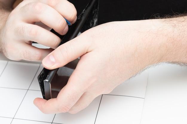 Analisando um telefone celular. o assistente abre a capa do smartphone usando ferramentas especiais