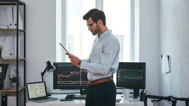 Analisar os dados de um jovem comerciante bem-sucedido em trajes formais está olhando os gráficos e relatórios comerciais