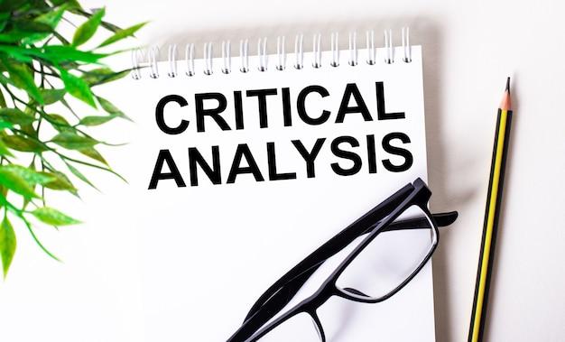 Análise crítica está escrita em um caderno branco ao lado de um lápis, óculos de armação preta e uma planta verde.