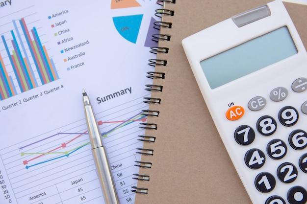 Análise de dados com calculadora, caderno e caneta.