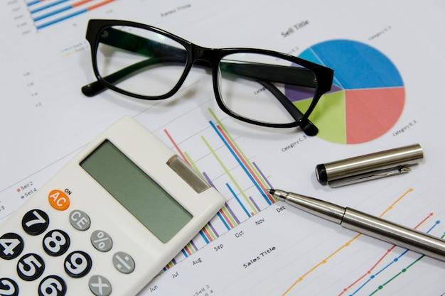 Análise de dados com calculadora, óculos e caneta