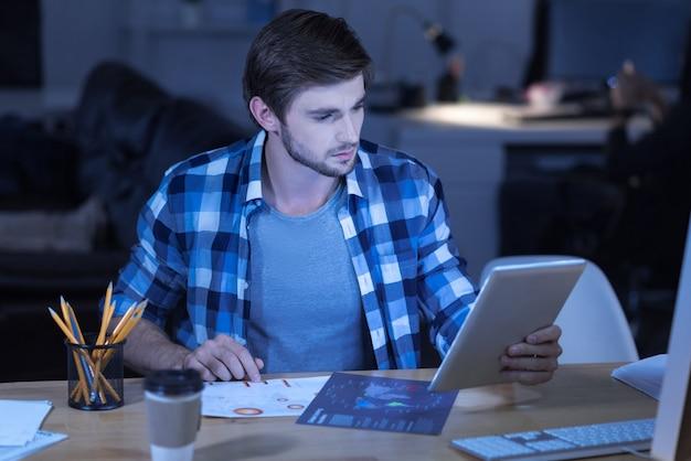 Análise de dados. homem bonito e inteligente que trabalha duro segurando o tablet e olhando seus documentos enquanto analisa os dados