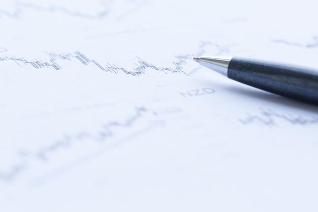 Análise de gráficos financeiros com caneta closeup