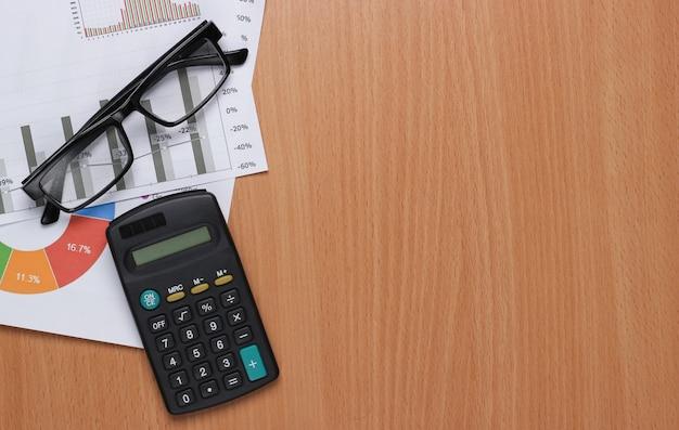 Análise de negócio. análise financeira. calculadora, óculos com gráficos e tabelas na mesa.