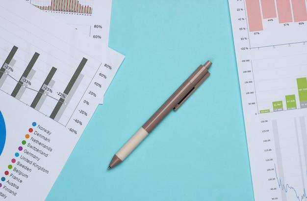 Análise de negócio. análise financeira. caneta com gráficos e tabelas em fundo azul. vista do topo