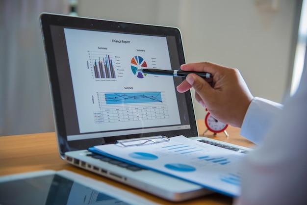 Análise de negócios - calculadora, folha, gráficos (relatório de negócios) e mão de analista