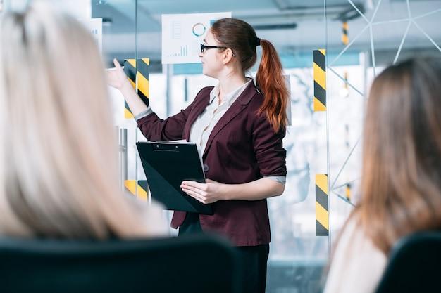 Análise de receita de negócios. apresentação da sala de reuniões. palestrante mostrando documentos com diagramas.