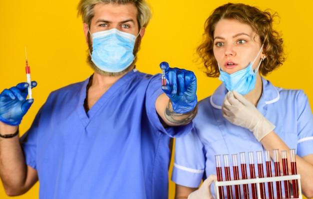 Análise de sangue. máscara respiratória de médicos. vacina contra infecção e exame de sangue. vacinação de tubos de ensaio de casal de médicos. amostras de sangue. criação de vacina. colegas de trabalhadores profissionais médicos.