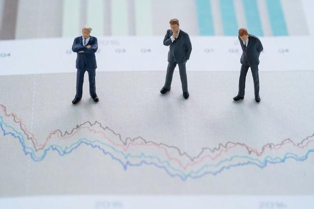Análise do conceito de investimento no mercado de ações, figura em miniatura de três empresários em pé