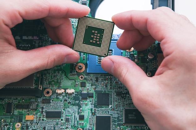 Análise do técnico e plugue do microprocessador da cpu no soquete da placa-mãe. plano de fundo da oficina
