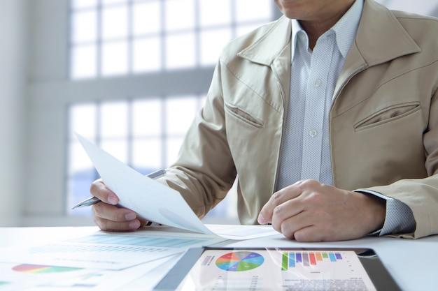 Analista segurando um documento enquanto analisa relatórios financeiros