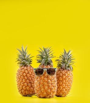 Ananases criativos com óculos de sol isolados em fundo amarelo, padrão de design de ideia de praia de férias de verão, espaço de cópia, close-up, em branco para texto