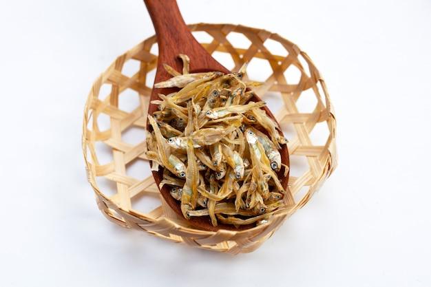Anchova seca em cesta de bambu em fundo branco