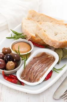 Anchovas, azeitonas, pão e patê de peixe no prato