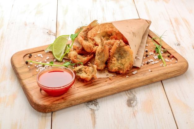 Anchovas crocantes fritas na mesa com folhas salat. fundo de papel. pequenos peixes em farinha de milho panorâmica sobre a fritura.