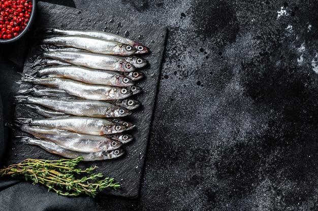 Anchovas de peixe pequeno cru com pimenta e tomilho. fundo preto. vista do topo. copie o espaço
