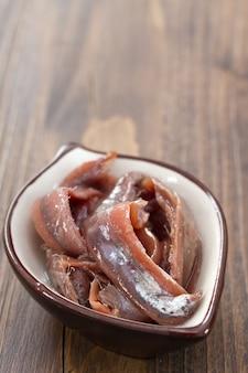 Anchovas em prato na madeira marrom