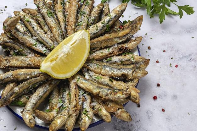 Anchovas fritas tradicionais com limão e salsa. conceito de frutos do mar