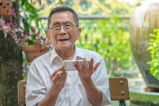 Ancião asiático idoso feliz que usa o smartphone em exterior.