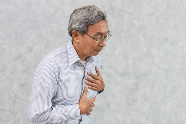 Ancião asiático sofre de dor no peito de ataque cardíaco ou derrame.