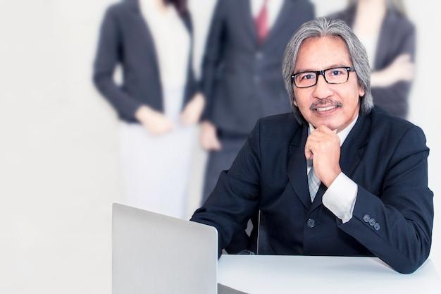 Ancião superior do negócio sério no escritório. ele olhando sorrindo