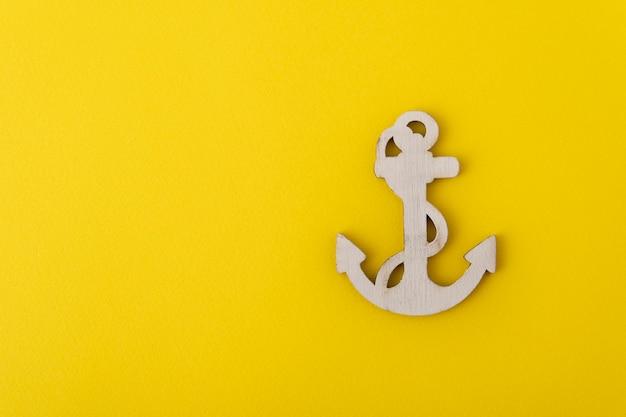 Âncora de madeira em fundo amarelo. conceito de cruzeiros marítimos. tema marinho.
