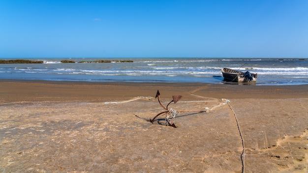 Âncora e barco de pesca à beira-mar