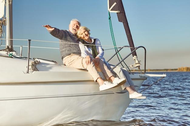 Ancora longe, feliz casal de idosos se abraçando no barco a vela ou no convés do iate flutuando no mar homem abraçando o seu