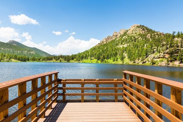 Ancoradouro de madeira no lago contra as montanhas rochosas