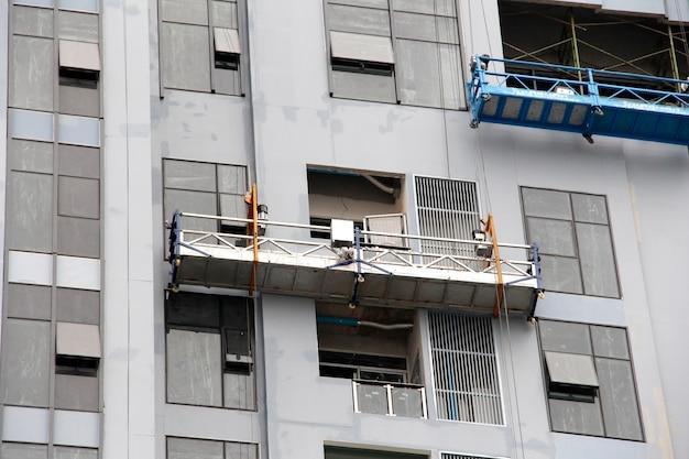 Andaime para limpar a janela no edifício alto.