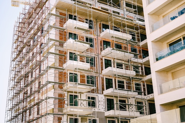 Andaimes em torno de um edifício alto e moderno em construção
