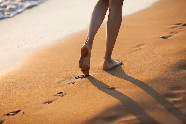 Andando descalço ao longo das ondas na praia de areia ao pôr do sol