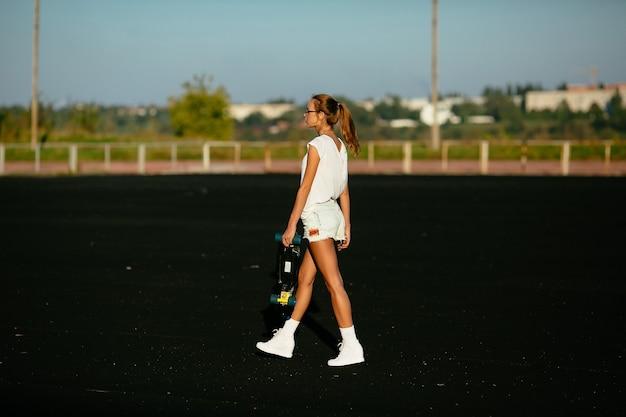 Andando mulher vista do lado. preparando-se para um skate.