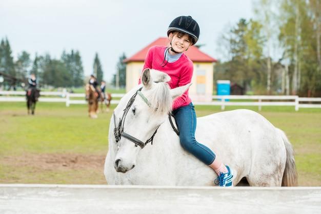 Andar a cavalo, linda equestre - menina está montando um cavalo