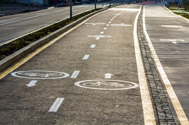 Andar a pé e sinais de ciclovia na superfície da estrada