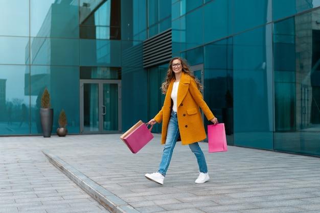 Andar ao ar livre mulher de negócios com sacos de compras vestido com casaco amarelo corporativo superfície de edifício caucasiano feminino pessoa de negócios edifício de escritórios elegante mulher de negócios venda de comprimento total