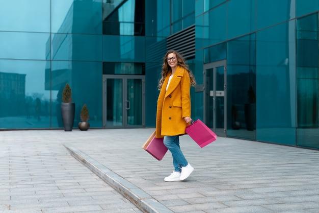 Andar ao ar livre mulher de negócios com sacos de compras vestido com casaco amarelo fundo de edifício corporativo caucasiano feminino pessoa de negócios edifício de escritórios elegante mulher de negócios venda de comprimento total